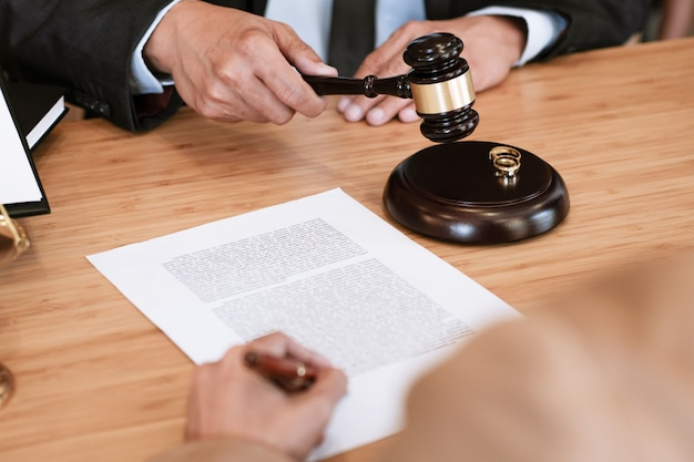 Gavel do juiz que decide em papéis de assinatura do divórcio do casamento. advogado