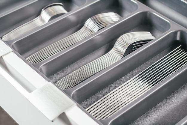 Gaveta aberta do armário de cozinha branco com bandeja organizadora de talheres preta com garfos, colheres e facas de prata. sistema de organização de armazenamento de cozinha