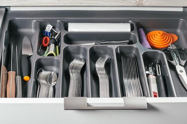 Gaveta aberta do armário de cozinha branco com bandeja organizadora de talheres preta com garfos de prata, colheres, facas e outros acessórios. sistema de organização de armazenamento de cozinha
