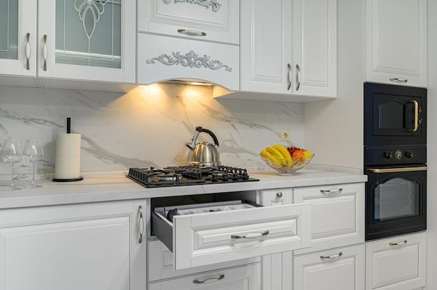 Gavetas abertas com utensílios de cozinha na cozinha branca moderna