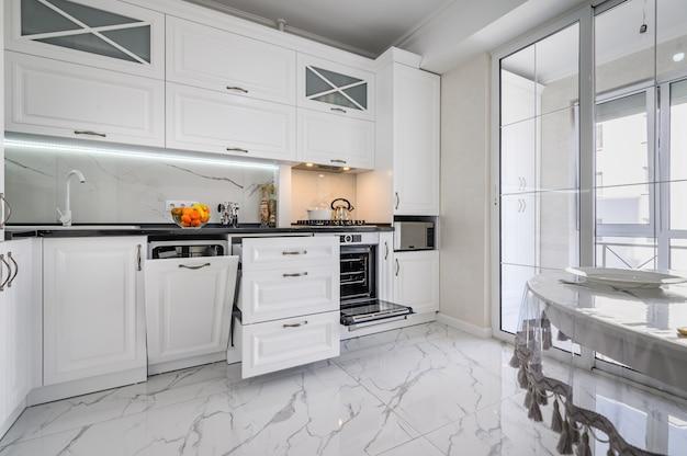 Gavetas interiores de cozinha brancas luxuosas e modernas puxadas para fora e a porta da máquina de lavar louça aberta