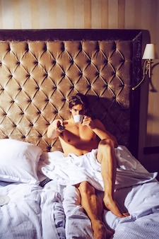 Gay com peito nu musculoso em corpo sexy em lençol branco