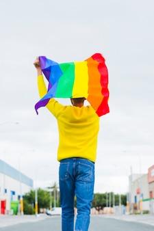 Gay indo na estrada segurando bandeira lgbt sobre a cabeça
