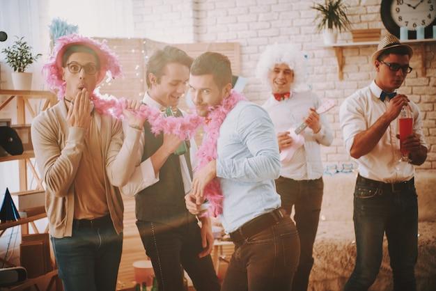 Gays bonitos têm uma festa em casa.