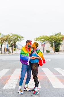 Gays com bandeira de arco-íris beijando na rua