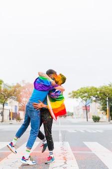 Gays com bandeiras de arco-íris abraçando na passagem para pedestres