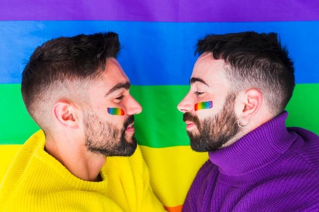 Gays com emblemas do arco-íris, olhando um para o outro
