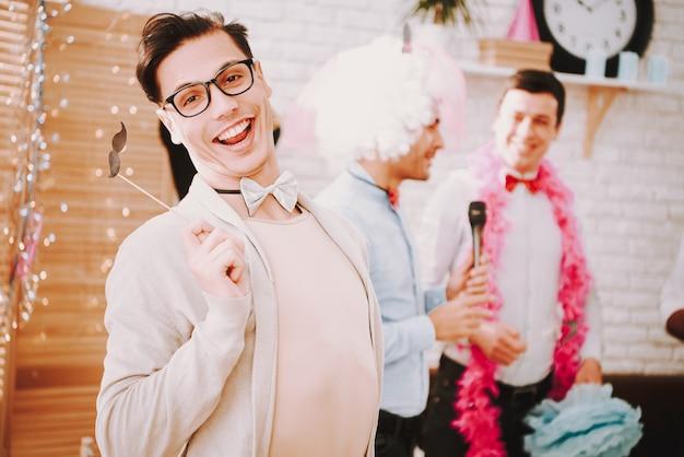 Gays com gravatas cantando músicas de karaokê na festa.