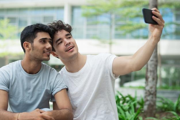 Gays interraciais felizes posando para selfie bonito na cidade