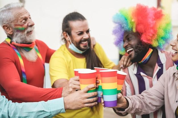 Gays multirraciais torcendo com óculos de arco-íris na parada do orgulho ao ar livre durante o surto de coronavírus - foco nos óculos