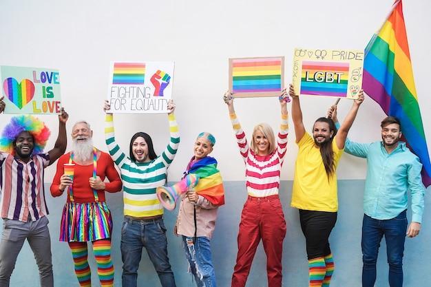 Gays se divertindo na parada do orgulho com bandeiras e faixas lgbt ao ar livre - foco principal na mulher do centro