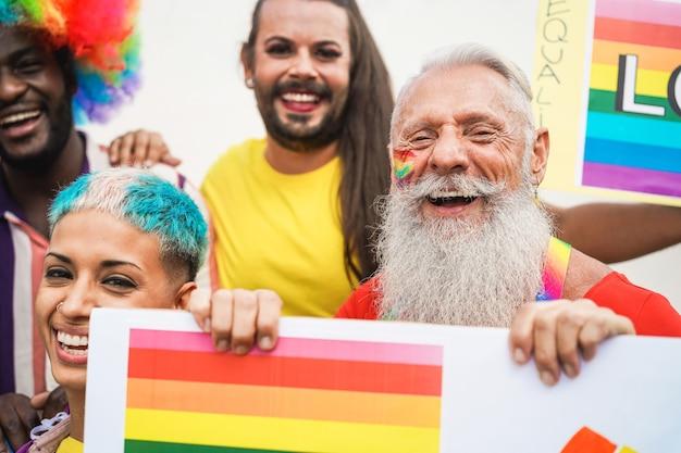 Gays se divertindo na parada do orgulho com banner lgbt ao ar livre - foco principal no rosto de um homem idoso