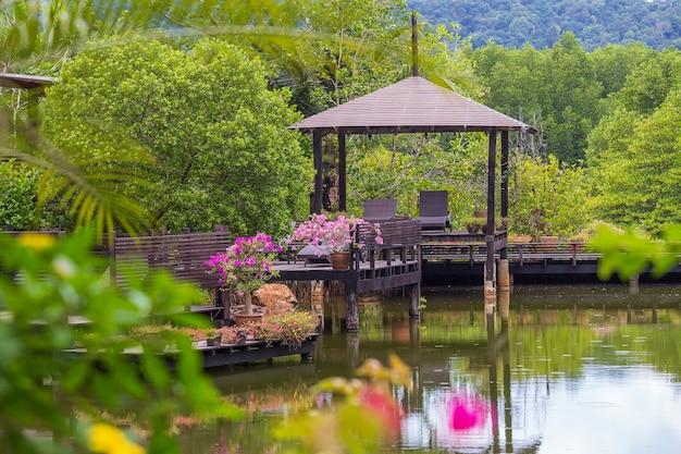 Gazebo de madeira com espreguiçadeiras para relaxar em um terraço com flores ao lado de um lago na ilha tropical da tailândia. natureza e conceito de viagens