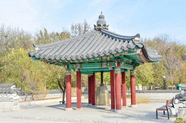 Gazebo de madeira coreano tradicional com ornamento pintado e sino amizade dentro