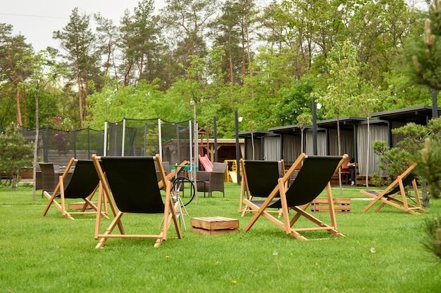 Gazebo de madeira no clube de golfe do campo nos subúrbios. o local para lazer longe, espreguiçadeiras. tipos no parquinho saltando e pulando na cama elástica no quintal