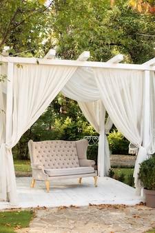 Gazebo de verão com cortinas brancas esvoaçantes e sofá.