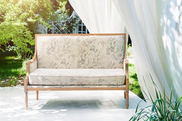 Gazebo moderno de luxo com móveis macios e cortinas dentro do jardim. pavilhão de cerimônia de casamento de verão.