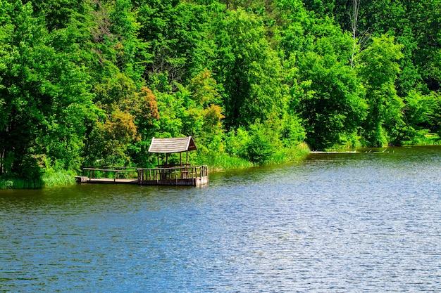 Gazebo relaxante construído no rio contra a floresta.
