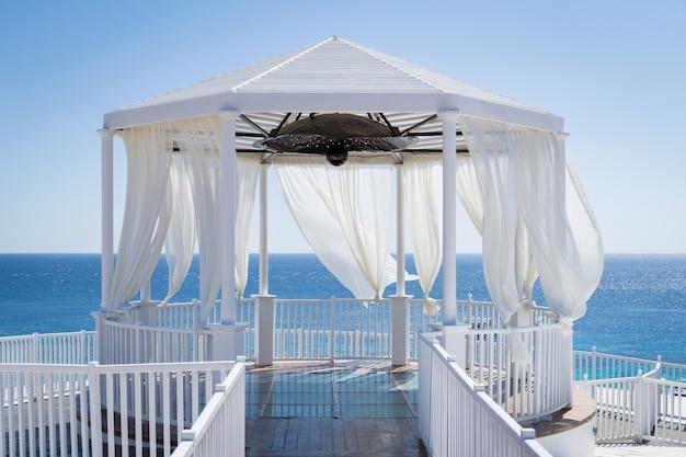 Gazebo romântico na praia com mar azul