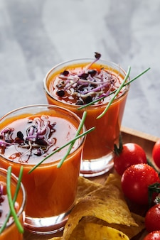 Gazpacho da sopa do tomate nos vidros com os sprouts brotados acompanhados com as microplaquetas de milho.