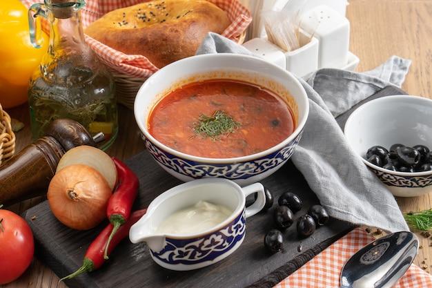 Gazpacho - sopa vegetariana de tomate com azeitonas, creme de leite e endro em um prato com um tradicional uzbeque