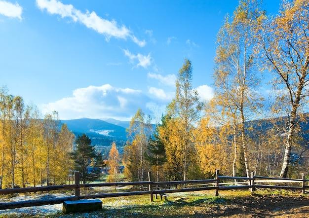 Geada de outono na clareira nos arredores de uma vila na montanha