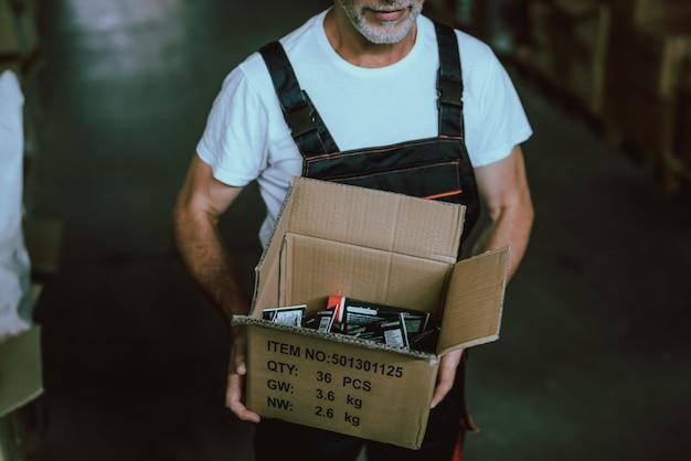 Ged man vestindo uniforme segurando a caixa de papelão