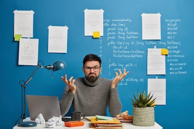 Geek masculino profissional estressante concentrado no monitor de um laptop moderno, usa óculos ópticos, posa no espaço de coworking contra um fundo azul