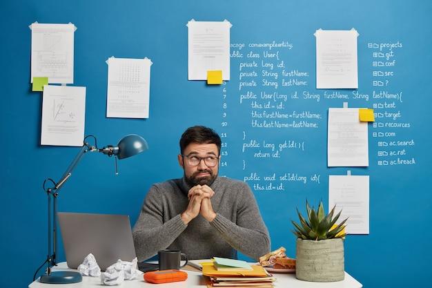 Geek masculino profissional sério concentrado no monitor de um laptop moderno, usa óculos ópticos, posa no espaço de coworking contra um fundo azul