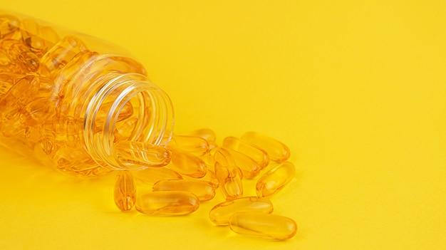 Géis moles de vitamina e e ômega 3 vazaram do recipiente sobre fundo amarelo.