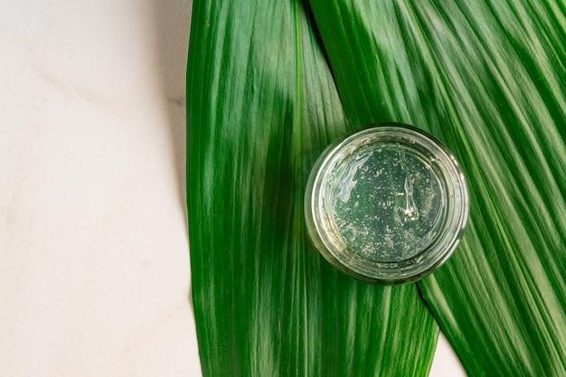 Gel com bolhas em um pequeno frasco transparente sobre folhas tropicais verdes