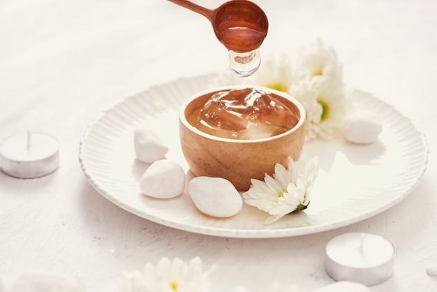 Gel de aloe vera em uma tigela, com crisântemo e vela na mesa de pedra