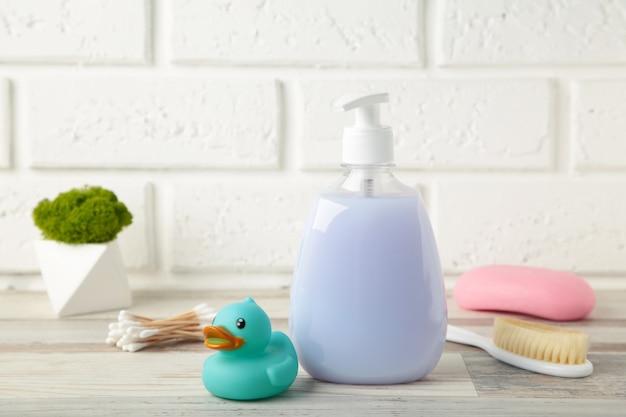 Gel de banho de bebê, sabonete, pato de borracha, pente na mesa. vista superior de cosméticos para bebês