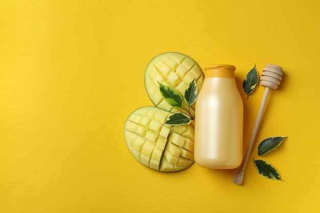 Gel de banho de manga natural e ingredientes em fundo amarelo