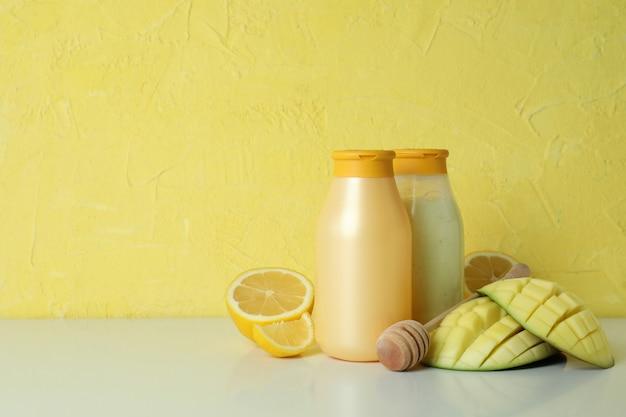 Gel de banho, manga e limão contra um fundo amarelo