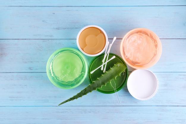 Gel de caracol, tapa-olho e fresh aloe vera gel em jarra sobre fundo azul de madeira