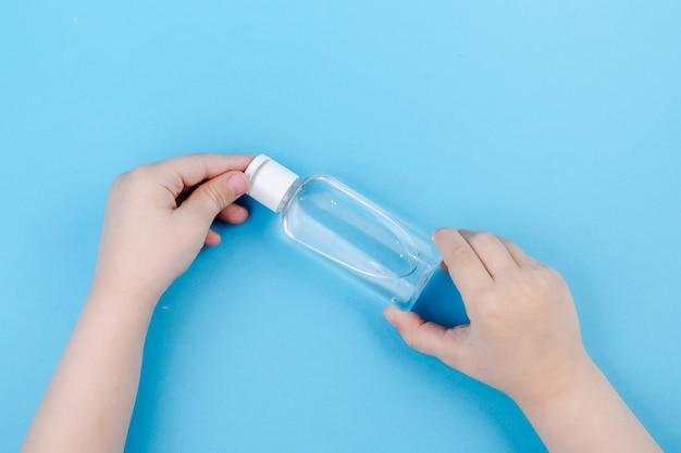 Gel de limpeza para mãos. despejando gel higienizante nas mãos da criança.