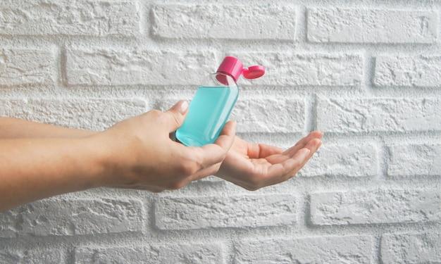 Gel desinfetante à base de álcool ou um gel antibacteriano para proteção contra bactérias ou vírus e coronavírus covid-19 em uma parede de tijolos brancos