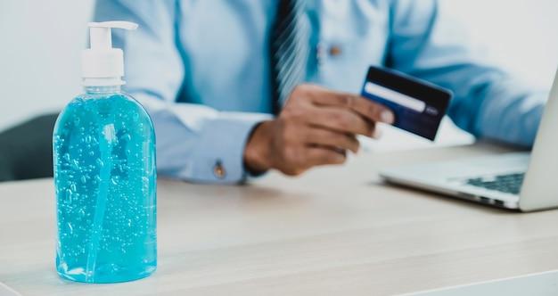 Gel desinfetante para as mãos em pé na mesa de madeira cartão de crédito da mão do empresário para compras online de casa, comércio eletrônico de pagamento, internet banking, gastar dinheiro com smartphone para as próximas férias.