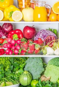 Geladeira cheia colorida com frutas e legumes