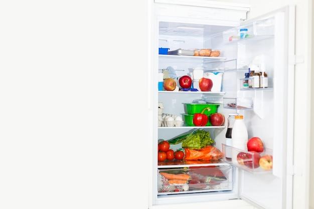 Geladeira de cozinha com freezer superior com portas abertas e prateleiras cheias de mantimentos com alimentos frescos e congelados e garrafas frias