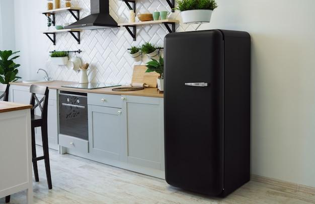 Geladeira preta de estilo retrô na cozinha cinza de madeira