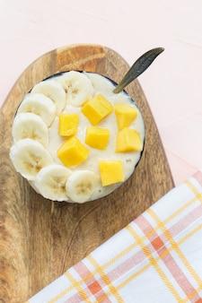 Gelado caseiro de banana e manga vegano amarelo sorvete sem leite na tigela de coco com colher, pedaços frescos de manga e banana em cima, fundo rosa. copie o espaço, foco seletivo