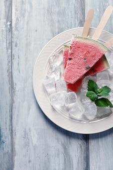 Gelado caseiro dos picolés congelados da melancia com a hortelã na placa branca.