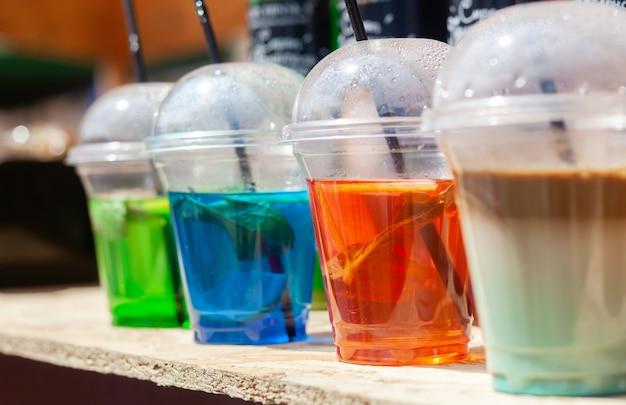 Gelado cocktails coloridos na mesa de madeira ao ar livre