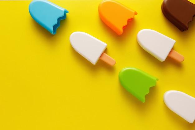 Gelado colorido e de vários brinquedos plástico com números para bebês em um fundo amarelo.