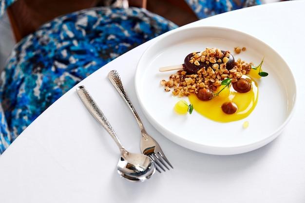 Gelado de foie gras com avelã e molho de laranja, em um prato branco com talheres