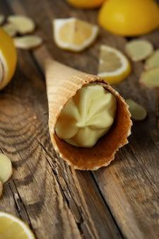 Gelado de gengibre limão em um cone de waffle com fatias de gengibre frescas e limões