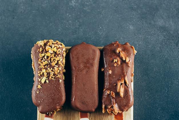 Gelado eskimo no esmalte do chocolate no fundo azul. delícia doce saboroso do petisco da comida.