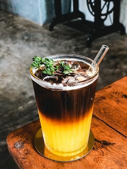 Gelado suco de laranja fresco coberto com café na mesa de madeira no café moderno.